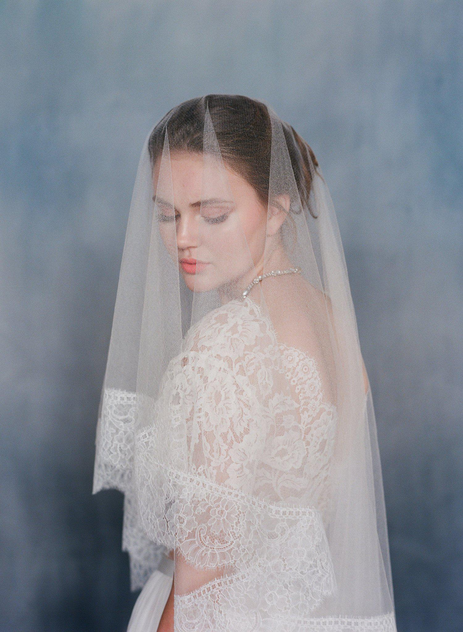 Women wearing a sheer silk veil with ivory lace trim