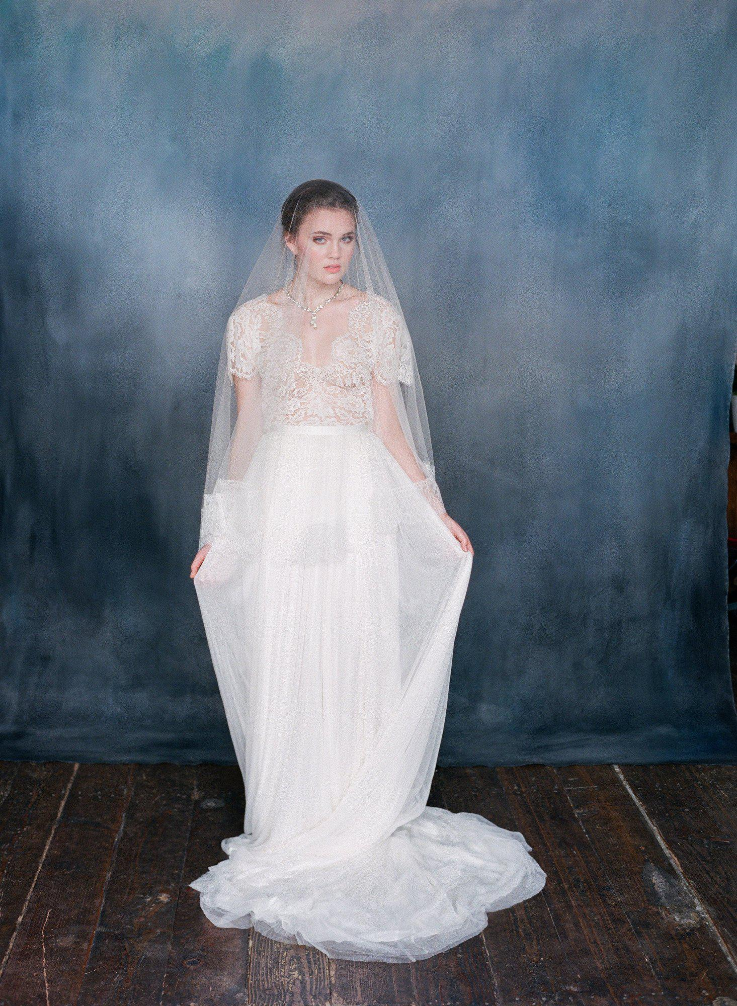 Women wearing am ivory silk tulle dress with sheer silk veil