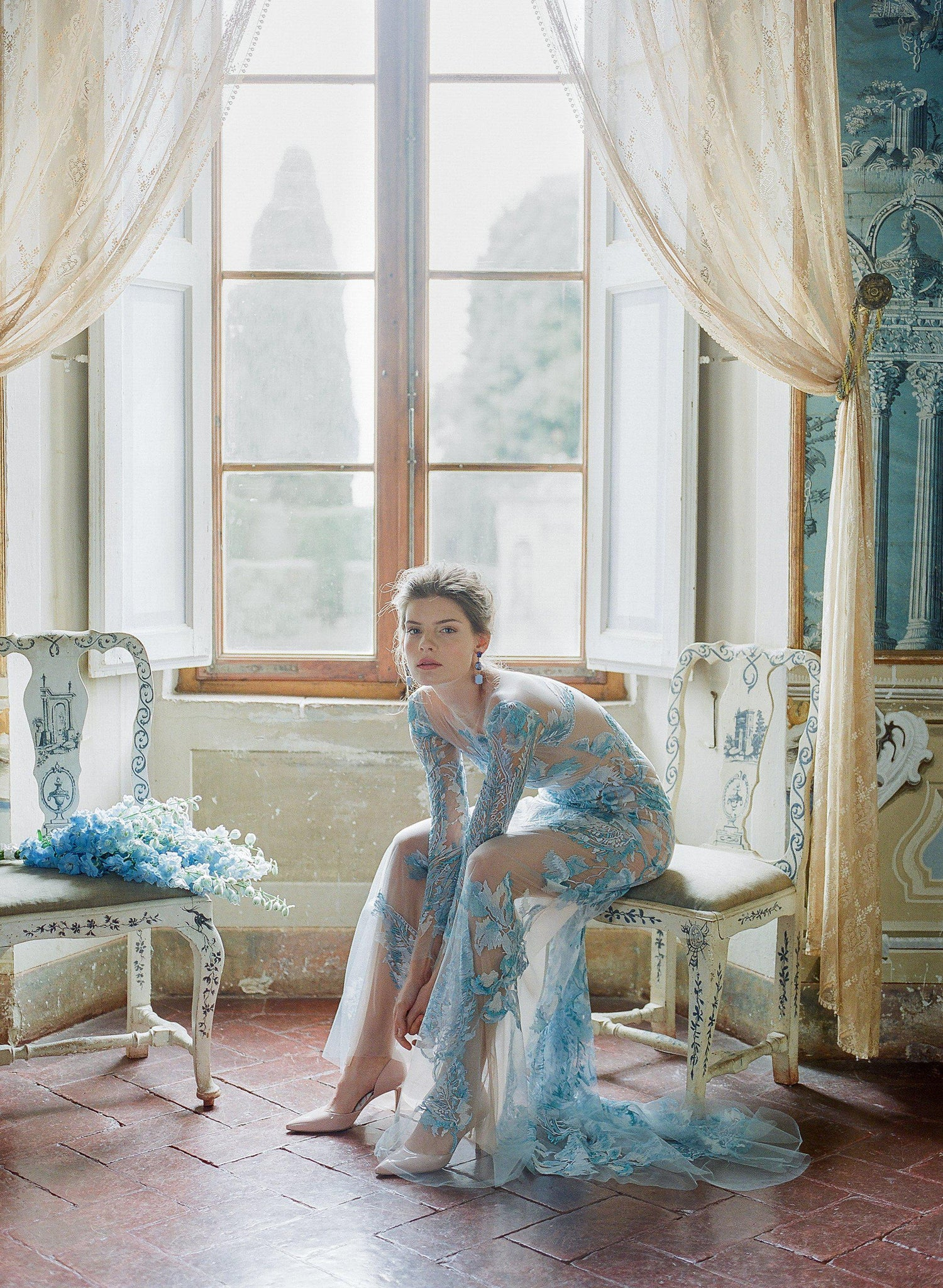 women sitting in chair wearing blue tulle dress at Villa di geggiano Siena Italy