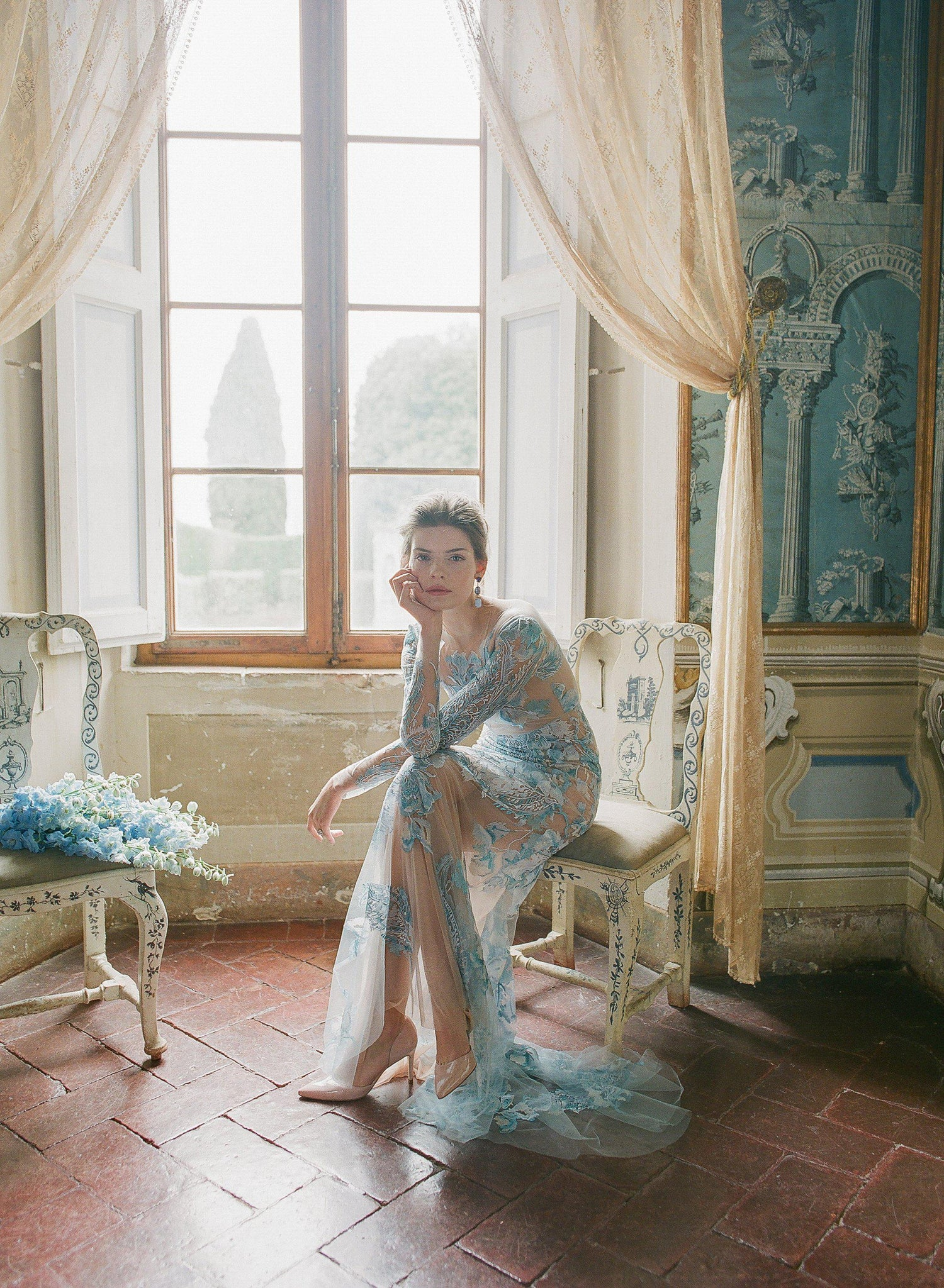 women sitting wearing a pale blue lace dress