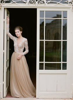 Women staying in doorway wearing a gold silk tulle dress with long sleeved beaded lace top.