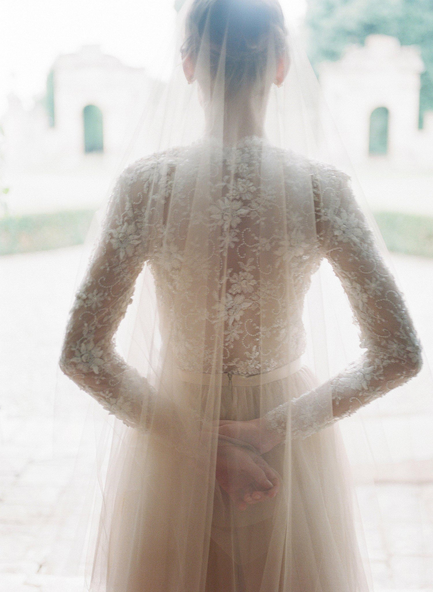 Back details showing brides sheer silk tulle veil with beaded lace top with sleeves
