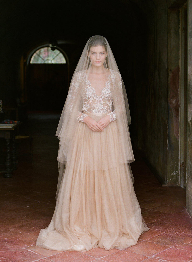 women wearing a silk tulle veil that matches her gold silk tulle dress with lace sleeves