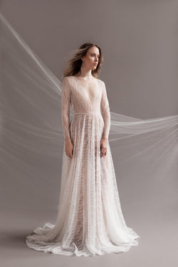 Women wearing a long sleeved Off-white sparkle dress with V-neckline and long sweeping train