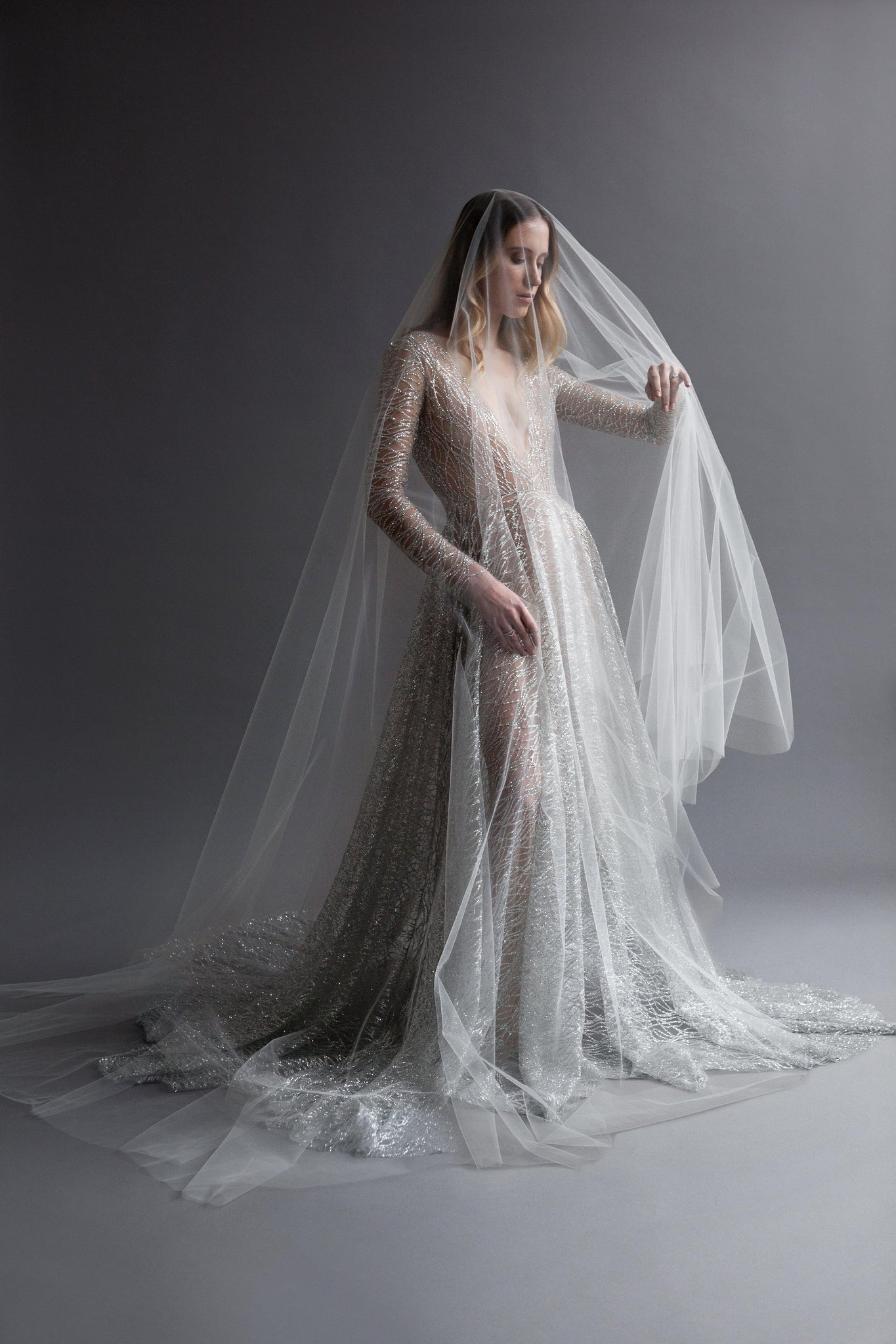 Women in Gray sparkle wedding dress that shimmers with large sheer veil
