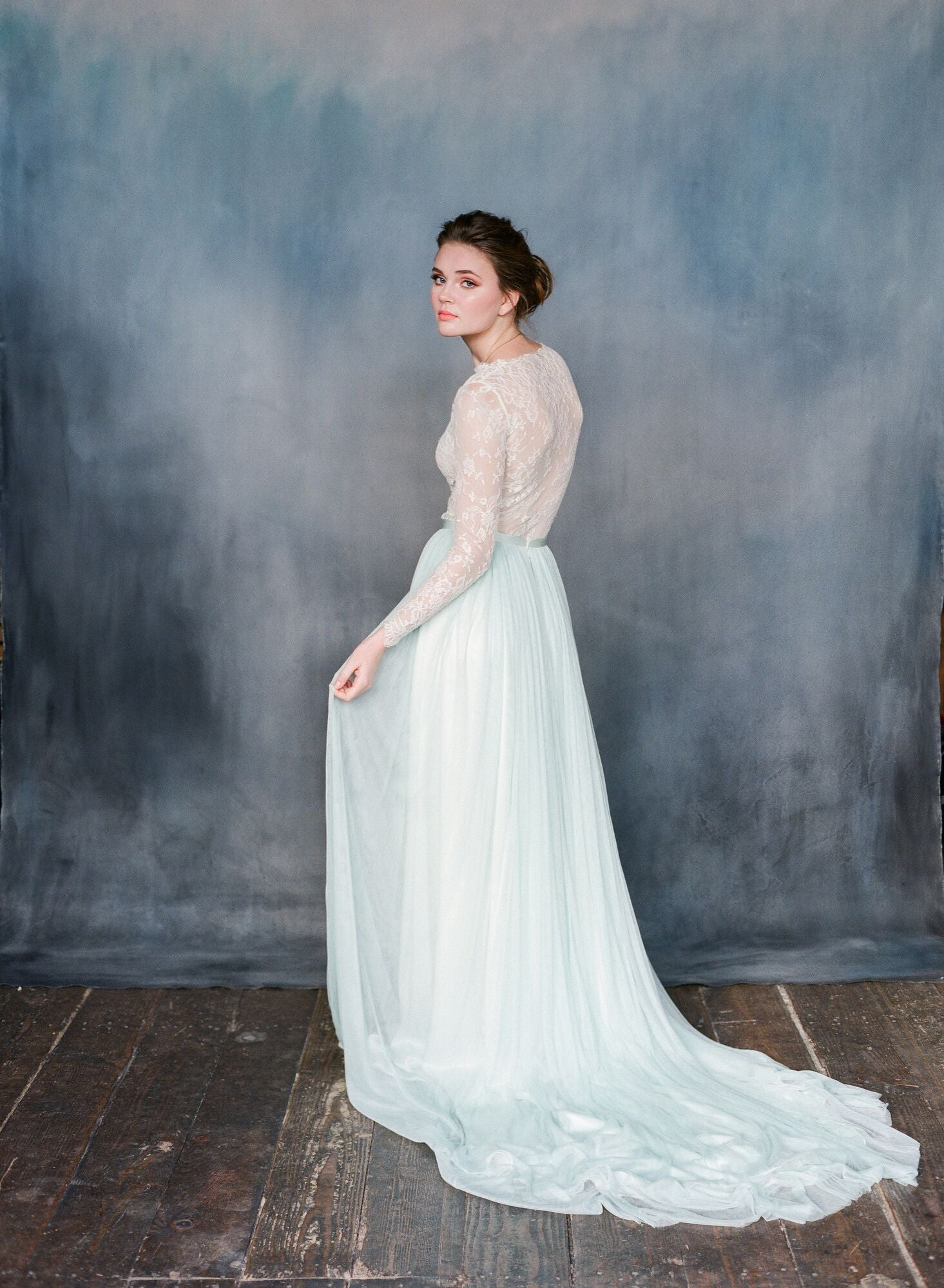 Side view of women wearing mint silk tulle dress with a long sleeved lace top