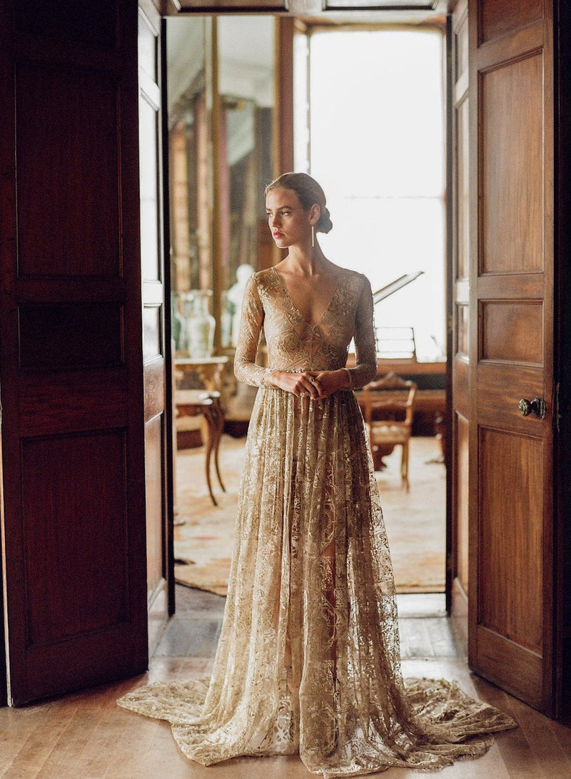 Women wearing long gold lace dress with longe sleeves and v-neck