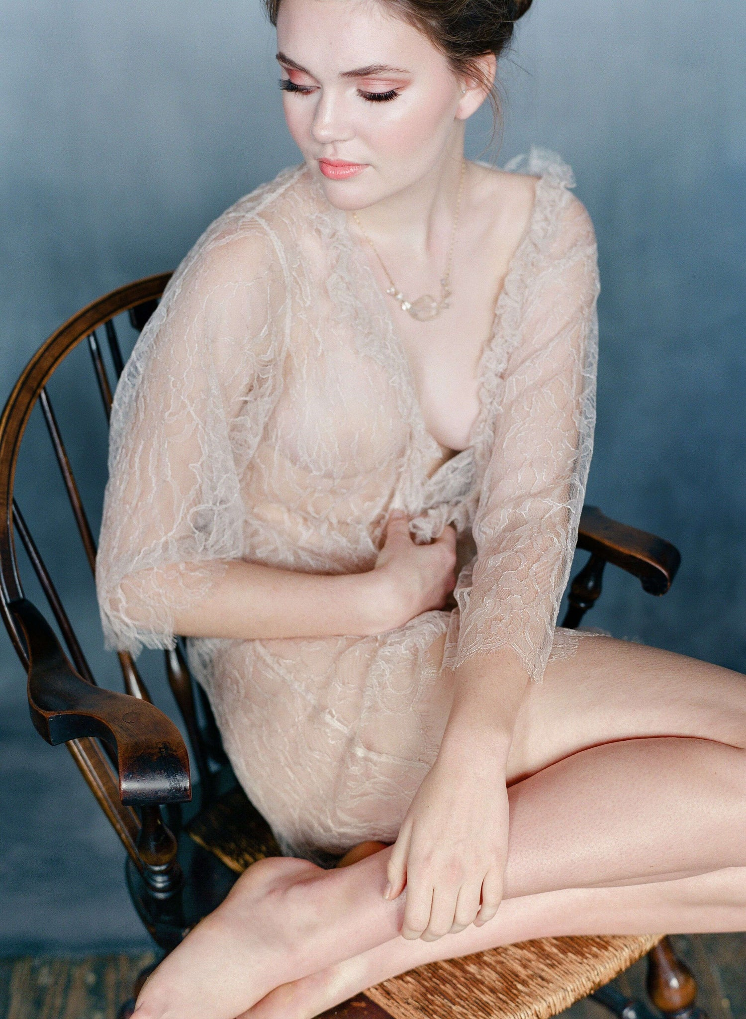 Women sitting in chair wearing blush lace robe