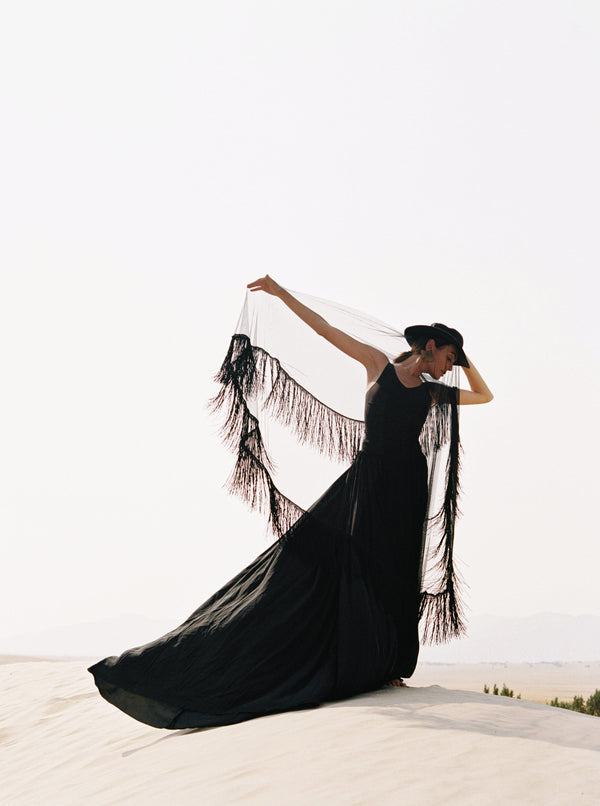 Women in the desert wearing a long black gathered skirt with a black fringe silk tulle veil