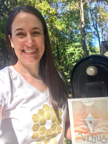 Astronomer Misty Bentz smiles in front of a mailbox holding a NASA JPL Venus Travel postcard and wearing a white v-neck JWST t-shirt