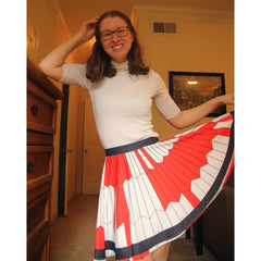 Erin posing in her Mars 2020 parachute skirt, with one hand on her head and the other holding the hem of the skirt out to show off the pattern.