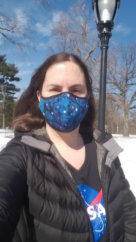 Emily wearing a blue starry mask and a NASA meatball t-shirt