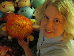 Noreen Grice holds the Sun plush toy in front of some of the other planets