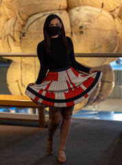 Woman with dark hair and a face mask wearing a long sleeve black shirt and a red and white skirt in the geometric design of the Perseverance Rover Parachute.