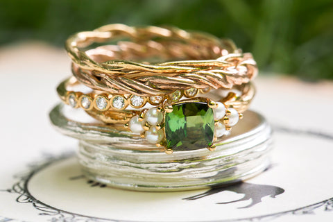 stack of organic wedding bands and engagement ring