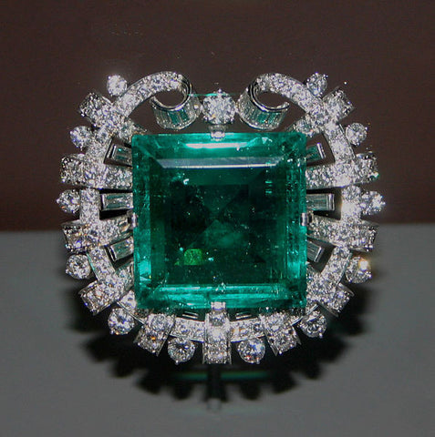 A beveled square-cut emerald in a platinum setting, surrounded by 109 round and 20 baguette cut diamonds.