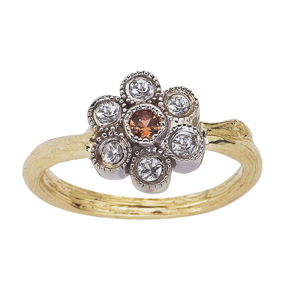 Daisy ring in 18K recycled gold. Each petal is set with one white sapphire. The center of the flower is a bright orange sapphire. This pretty sapphire flower is set on a twig band. BMJNYC