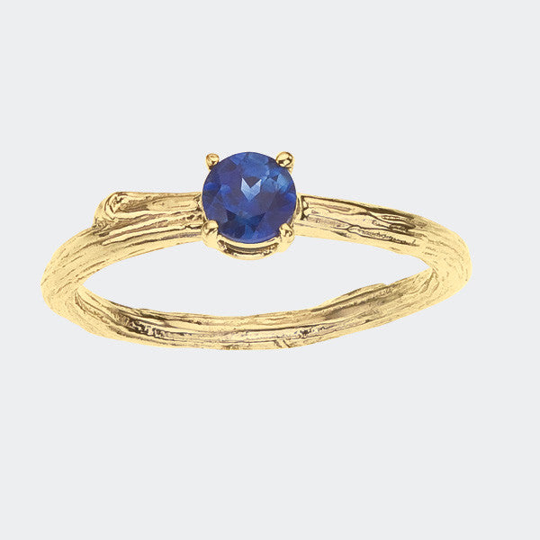 simple twig engagement ring with blue sapphire in yellow gold