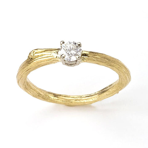 A classic diamond ring with an organic twist.  A brilliant white diamond is prong set on a thin branch band.