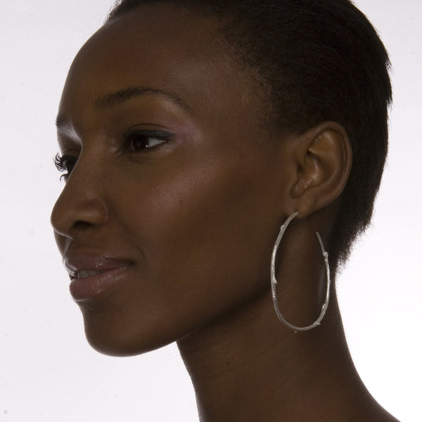 The model is wearing Barbara Polinsky's Sterling Silver Extra Large Twig Hoop Earrings.