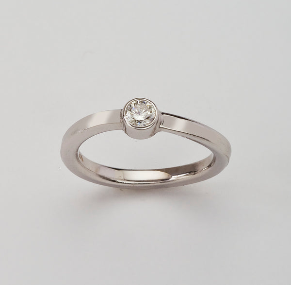 Simple diamond engagement ring with bezel set diamond.