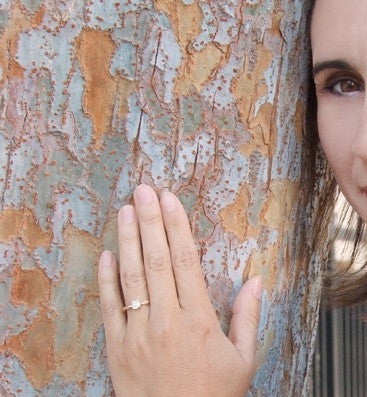 Model Wearing Cushion Cut Diamond Engagement Ring with Nature Inspired Twig Vine Band in Rose Gold.