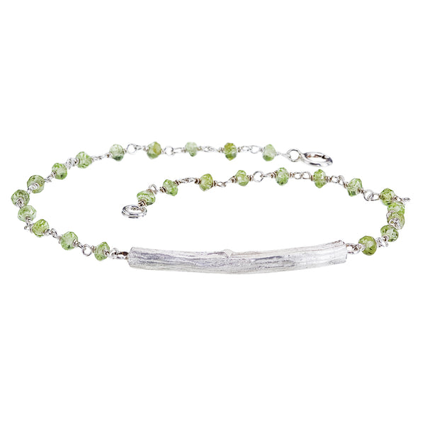 This bracelet of wire wrapped peridot beads is accented with a gleaming sterling silver twig.