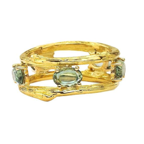 Two twig bands in 18K yellow gold present five oval green sapphires.  Designed by Barbara Polinsky.