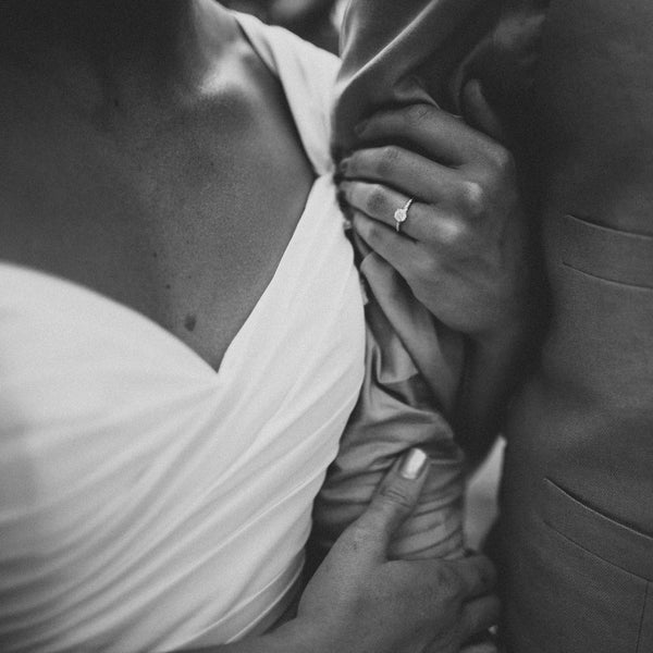 Beautiful Photo of Bride's Left Hand, Wearing Twisted Vine Diamond Engagement Ring, Holding onto Groom.