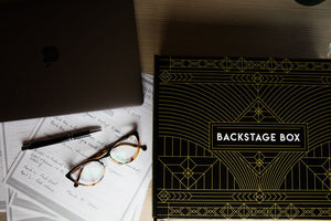 Image of a Backstage Box, pen, glasses, laptop and notes before taking a speech