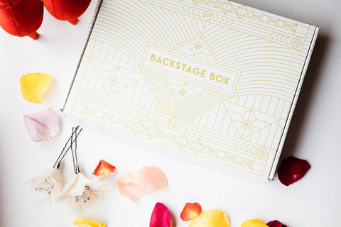 Backstage Box, a white box with gold lettering surrounded by multicolor rose petals and toiletry items.