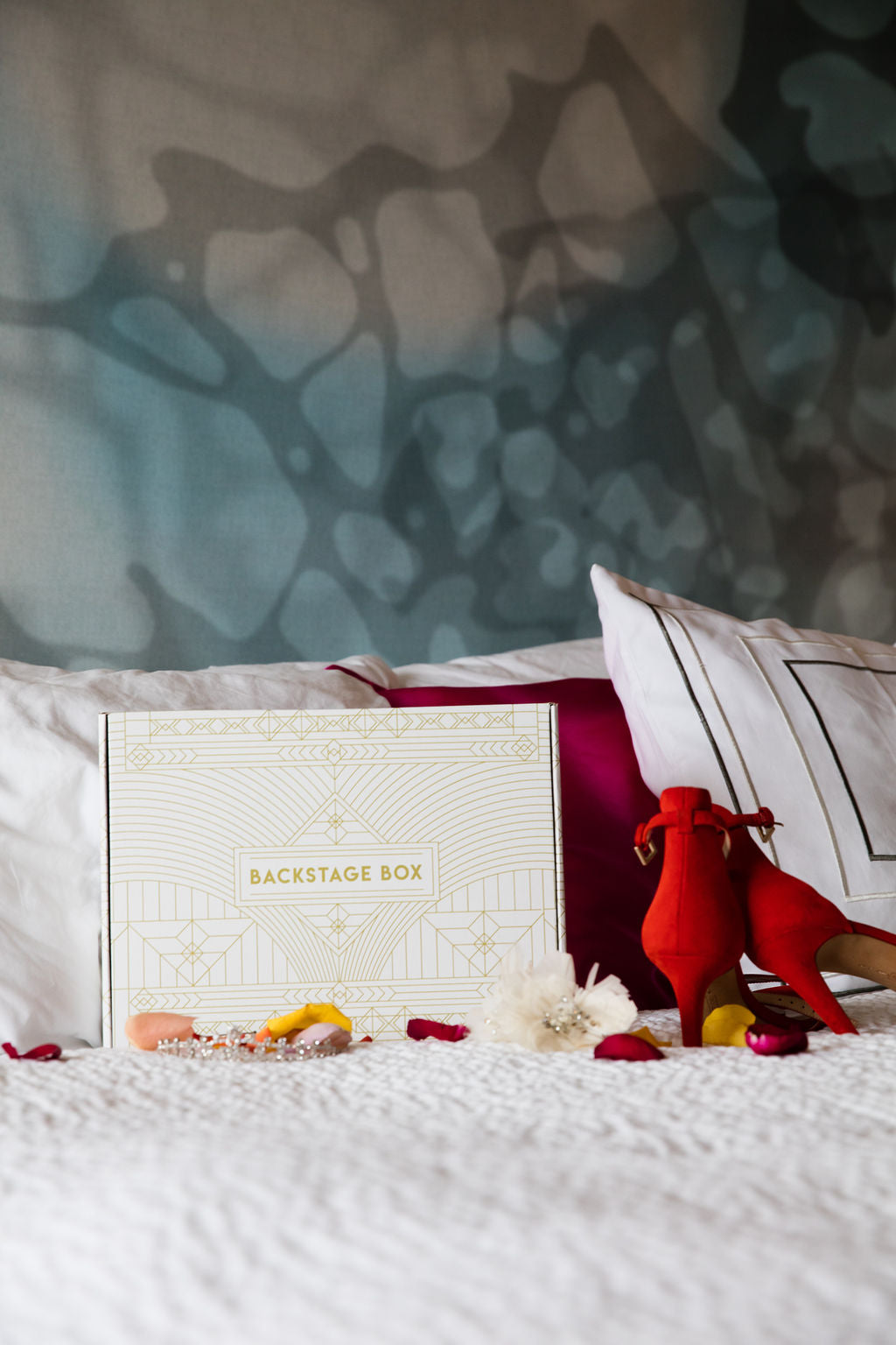 A white box with gold art deco designs and lettering on a bed with orange heels, rose petals and a crystal tiara.