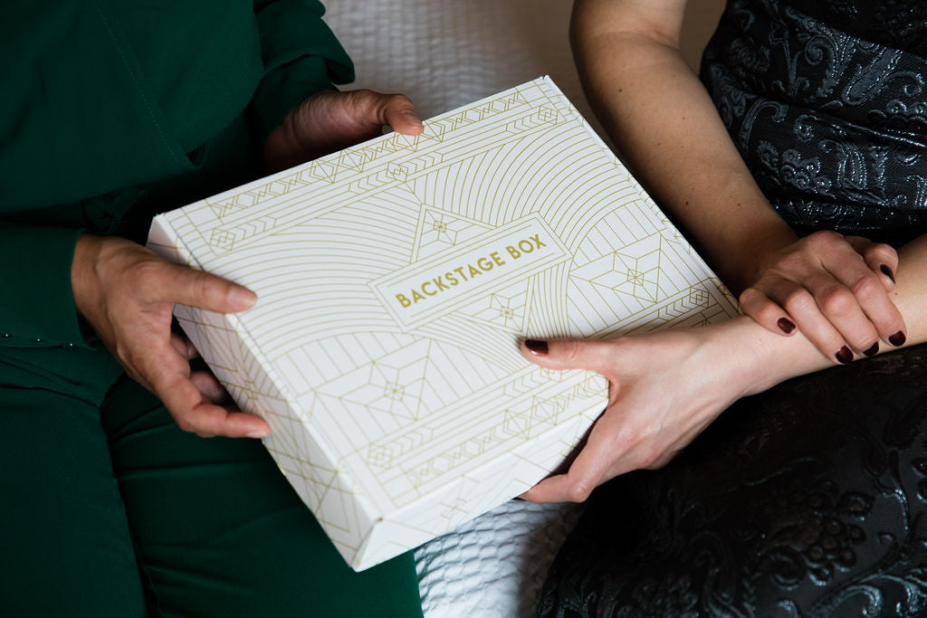 A white box with gold art deco designs and lettering held by two pairs of female presenting hands.