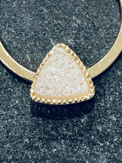 Close up of white druzy on gold hoop earring