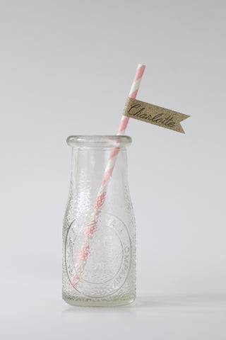 straw in clear glass bottle with gold tag