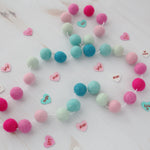 Aqua and pink valentine's felt ball garland with sweet heart stickers on a white wood table