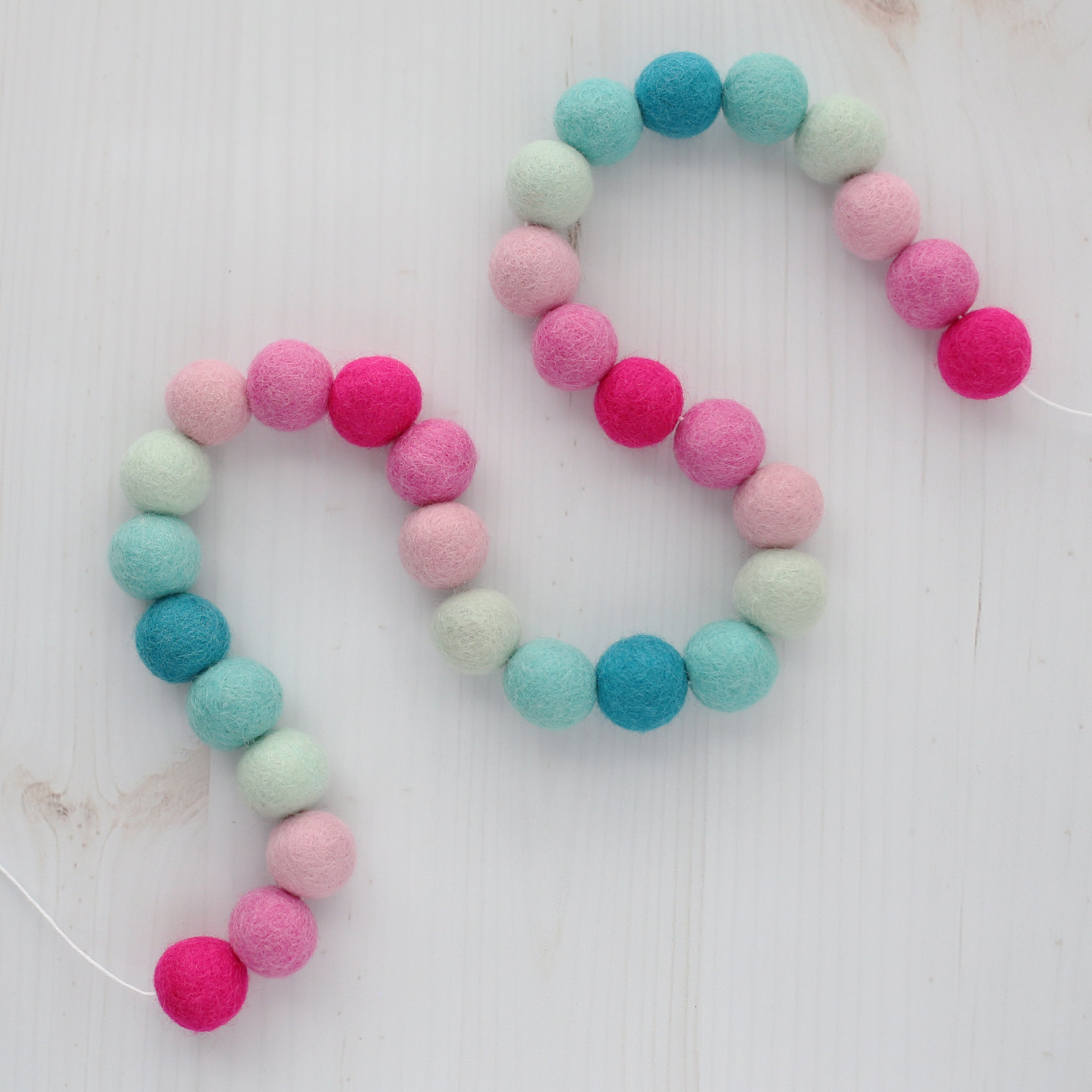 Aqua and pink valentine's felt ball garland on a white wood table