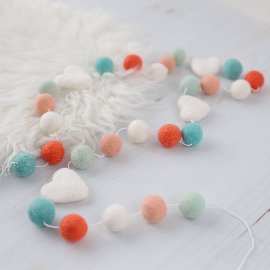 Aqua and peach valentine garland with white hearts on sheep skin rug