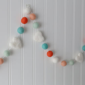 Aqua and peach valentine garland with white hearts hung on wall