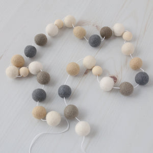 Hygge Neutral felt ball garland with wood beads on a white wood table