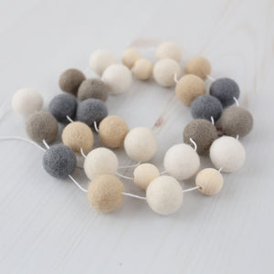 Hygge Neutral felt ball garland with wood beads wound in a circle