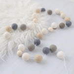 Hygge Neutral felt ball garland with wood beads on a sheep skin rug
