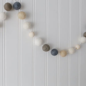 Hygge Neutral felt ball garland with wood beads hung on a wall