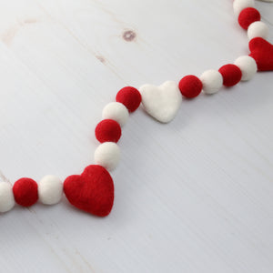 Red and white Valentine's Day felt ball garland with felt hearts on a white wood table
