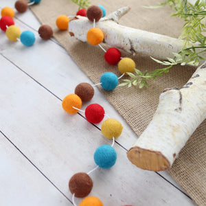 felt ball thanks giving garland in teal, orange, red, brown and mustard displayed on a rustic table with birch wood elements and burlap