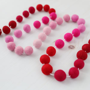 Valentine red and pink ombre felt ball garland on a white wood table