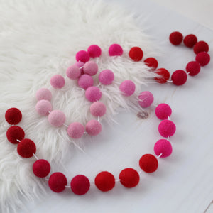 Valentine red and pink ombre felt ball garland on a sheep skin rug