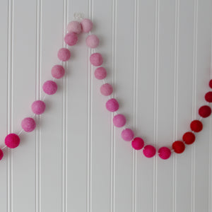 Valentine red and pink ombre felt ball garland on a white wall