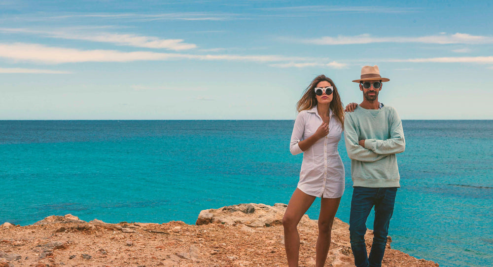 a couple stand on the beach wearing SOLFUL the best sunglasses to buy in Ibiza