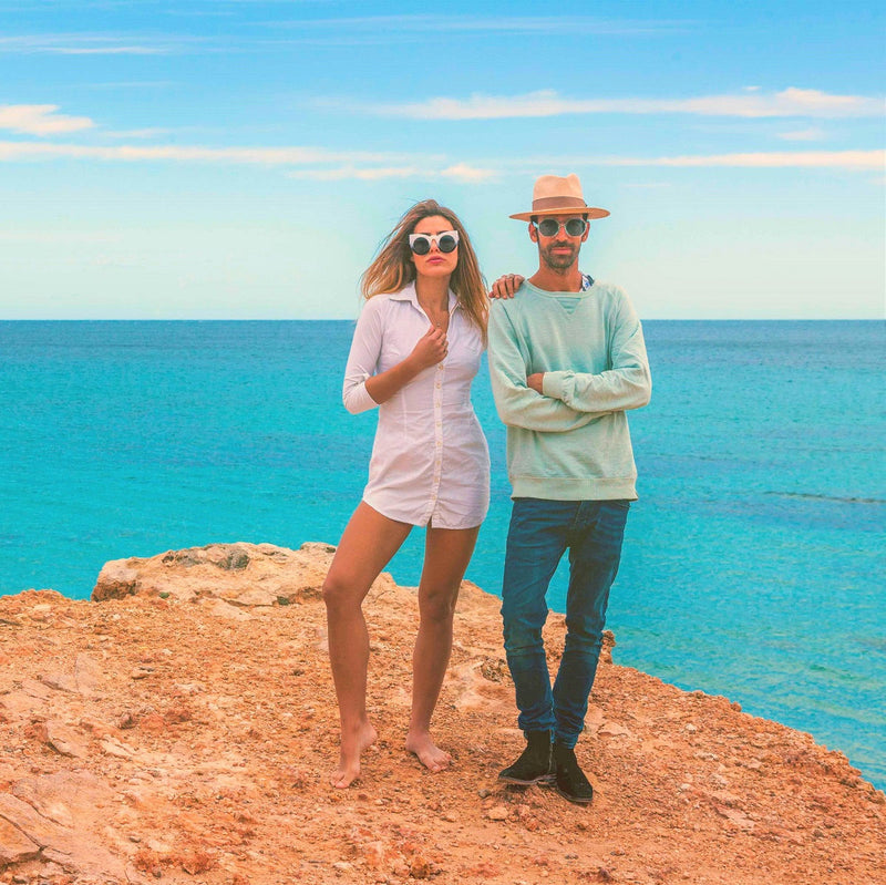 couple standing on the cliff in ibiza wearing solful sunglasses